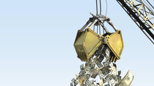 Crane grabber dropping various dollar bills