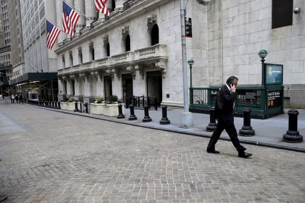 A trader talks on the phone as he walks outside the New York Stock Exchange.