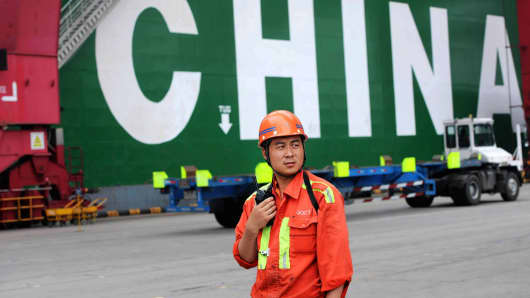 A docker works in front of a container ship at Qingdao Port in Qingdao, Shandong Province of China.