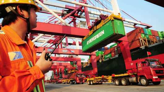 A worker monitoring the loading of containers on to a ship at the harbour in Qingdao, in northeast China's Shandong province.