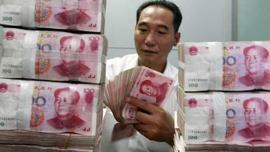 A Chinese bank staff member counting stacks of 100-yuan notes at a bank in Huaibei, east China's Anhui province.