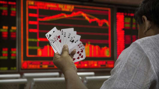 A Chinese day trader plays cards wit5h others as he watches a stock ticker at a local brokerage house in Beijing, China.