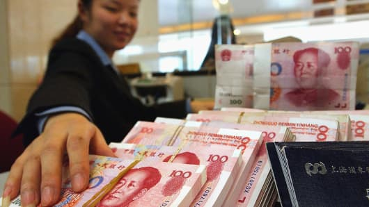 A bank teller counting stacks of Chinese currency notes at a local bank in the eastern city of Nanjing.
