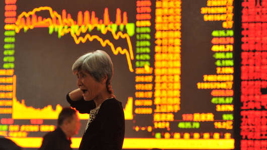 A stock investor gestures as she checks share prices at a security firm in Fuyang, east China's Anhui province.