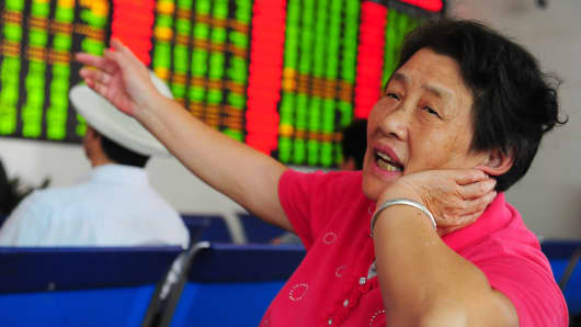 An investor observes stock market at a stock exchange hall in Fuyang, Anhui Province of China.