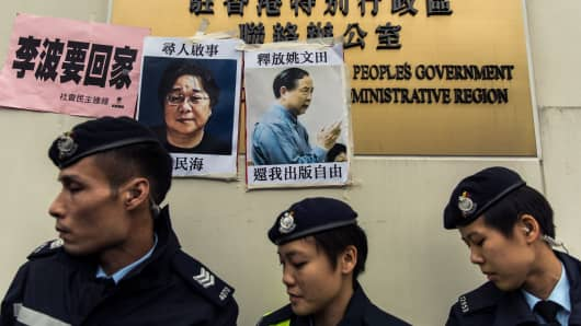 Police walk past missing person notices of Gui Minhai (L), one of five missing booksellers from the Mighty Current publishing house and Yau Wentian (R), a Hong Kong publisher who was last year jailed for 10 years while preparing to release a book critical of Chinese President Xi Jinping.
