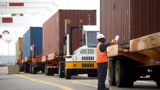 A spotter lines up a truck before a container is loaded from a ship in the Seagirt Marine Terminal at the Port of Baltimore.