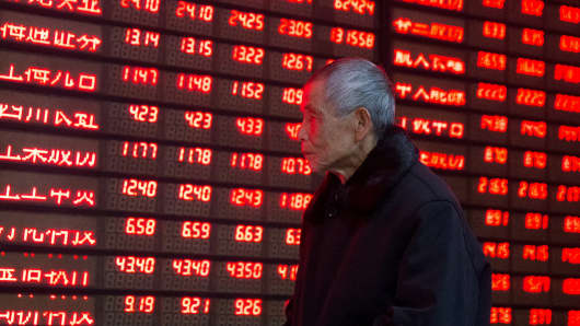 An investor walks past an electronic screen showing stock information at a brokerage house in Nanjing, Jiangsu province, January 19, 2016.