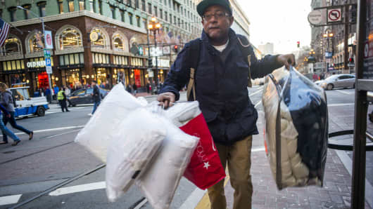 A pedestrian carries shopping bags while crossing Market Street in downtown San Francisco.