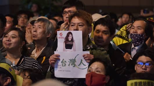 A supporter of Taiwan's Democratic Progressive Party (DPP) holds up a placard of K-pop artist Chou Tzu-yu.