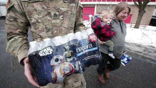 Michigan National Guard Staff Sergeant William Phillips of Birch Run, Michigan, helps Flint resident Amanda Roark and her son Dash take bottled water out to her vehicle after she received it at a Flint Fire Station January 13, 2016 in Flint, Michigan.