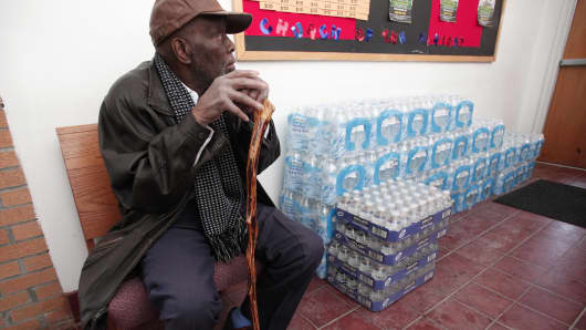 A man sits next to a stack of bottled water at a rally where the Rev. Jesse Jackson spoke about the water crises at the Heavenly Host Baptist Church January 17, 2016 in Flint, Michigan.