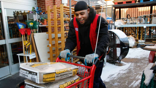 Employee Donald Mills wheels out bags of sand for a customer at Strosniders Hardware store in Silver Spring, Md., Jan. 21, 2016.