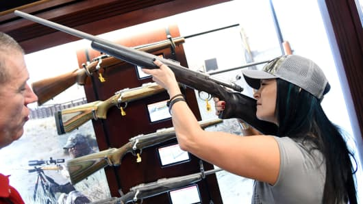 A woman tries out a rifle at a National Shooting Sports Foundation's Shooting, Hunting, Outdoor Trade Show in Las Vegas.