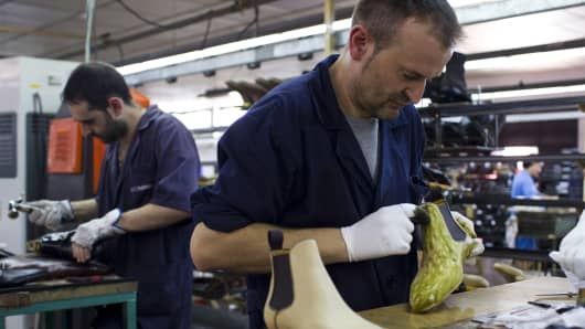 An employee rubs dye onto the leather uppers of a luxury shoe during the coloring process at the Magnanni factory, operated by Blanco Aldomar SL, in Almansa, Spain