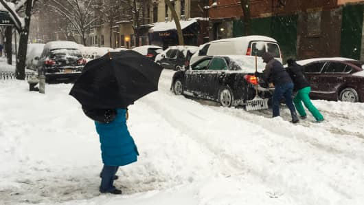 New Yorkers help a car stuck in the snow as winter storm Jonas pummels the Eastern U.S. on Jan. 23rd, 2016.