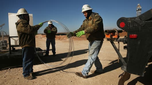 Employees of Stewarts Inc., an oil field service company, work on a chemical drum at a drilling site in the Permian Basin oil field on Jan. 20, 2016, in the oil town of Andrews, Texas.