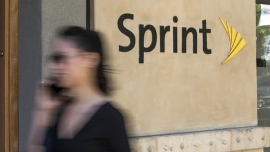 A woman talks on a mobile phone as she walks past a Sprint Corp. store in Palo Alto, California.