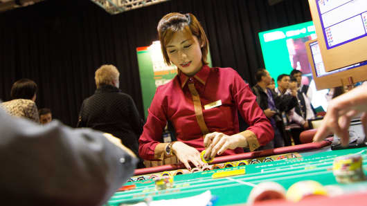A dealer handles gaming chips at a baccarat table inside the Venetian Macau resort and casino, operated by Sands China Ltd., a unit of Las Vegas Sands Corp., in Macau, China.