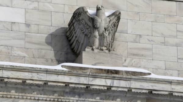Snow rests on the eagle statue atop the U.S. Federal Reserve in Washington January 26, 2016.