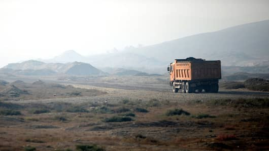 This picture taken on September 18, 2014 shows a truck carries ores from a quarry in the outskirts of Urumqi