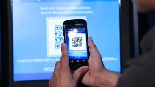 A person scans a quick response (QR) code with a smartphone while demonstrating usage of the company's Robocoin-branded automated teller machine (ATM) at The Pink Cow restaurant and bar in Tokyo, Japan.