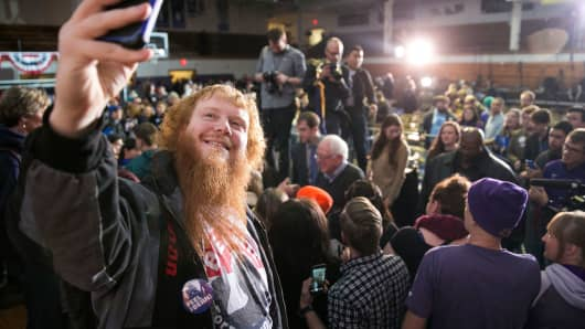 A young man takes a selfie with Democratic presidential candidate Sen. Bernie Sanders in the background after an event at the University of Northern Iowa, in Cedar Falls, Jan. 24, 2016.