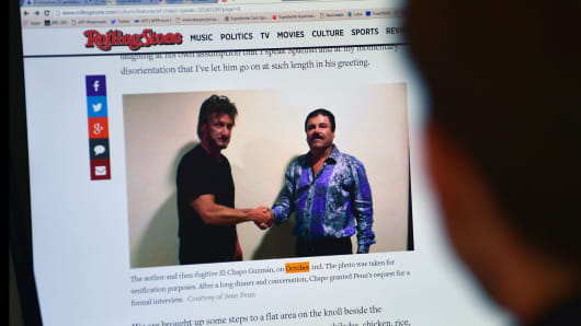 A man reads an article about drug lord Joaquin Guzman, aka 'El Chapo', showing a picture of him and actor Sean Penn, on the website of Rolling Stone magazine.