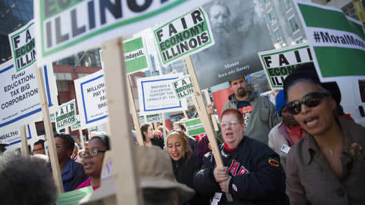 Demonstrators, protesting the state of Illinois budget stalemate, rally in the Loop before marching to the Chicago Board of Trade Building where they blocked all of the entrances on Nov. 2, 2015.