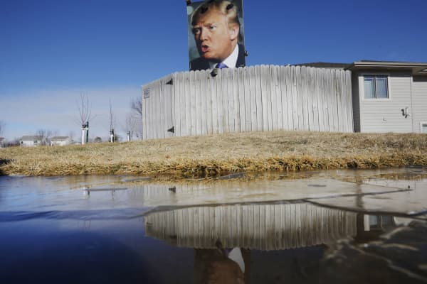 A large poster of U.S. Republican presidential candidate Donald Trump is reflected in an icy puddle in a residential neighborhood in West Des Moines, Iowa January 28, 2016.