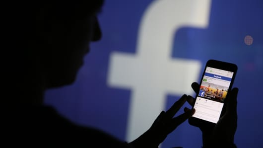 A woman checks the Facebook Inc. site on her smartphone whilst standing against an illuminated wall bearing the Facebook Inc. logo