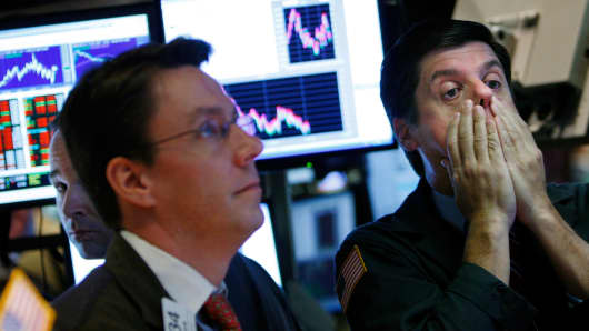 A trader holds his face while working on the floor of the New York Stock Exchange October 7, 2008 in New York City.