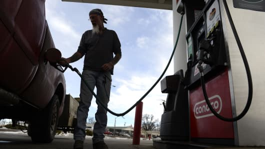 A man fills his truck up with gas at a gas station on January 25, 2016 in Kersey, Colorado.