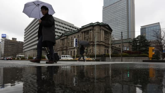 Pedestrians holding umbrellas while walking past the Bank of Japan (BOJ) headquarters are reflected in a puddle in Tokyo, Japan, on Friday, Jan. 29, 2016.