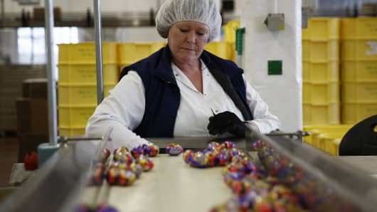 An employee monitors foil-wrapped Cadbury Creme Eggs as they move along the production line at the Bournville Cadbury factory, operated by Mondelez International.