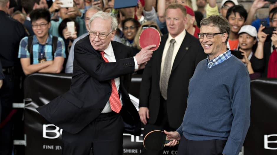 Warren Buffett, chairman of Berkshire Hathaway Inc. (left), plays pingpong with Bill Gates, chairman and founder of Microsoft Corp. and a Berkshire Hathaway Inc. director, at the Berkshire Hathaway annual shareholder meeting in Omaha, Nebraska, on May 3, 2015.