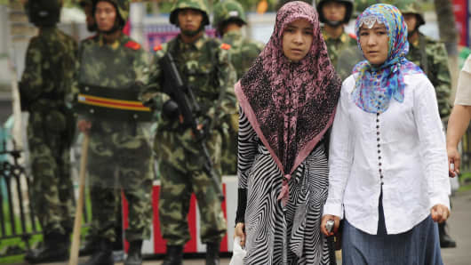 Two ethnic Uighur women pass Chinese paramilitary policemen standing guard outside the Grand Bazaar in the Uighur district of the city of Urumqi in China's Xinjiang region.