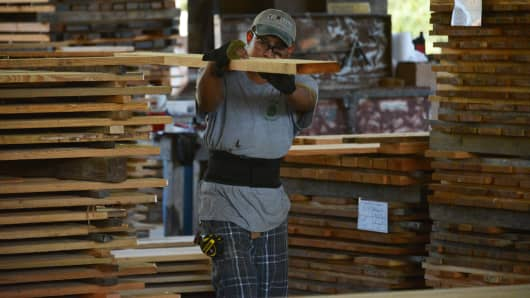 A worker carries a Heart Pine plank of lumber in the sawmill at the Goodwin Co. facility in Micanopy, Florida.