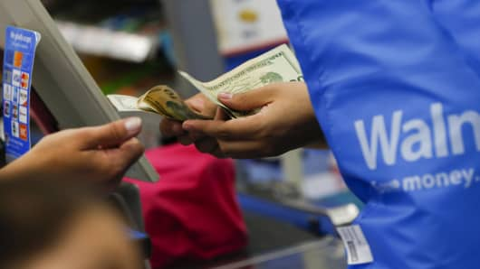 A customer receives cash change from a cashier at a Wal-Mart Stores Inc. location in the Porter Ranch neighborhood of Los Angeles, Calif.