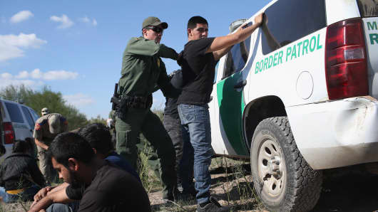 A U.S. Border Patrol officer body searches an undocumented immigrant after he illegally crossed the U.S.-Mexico border and was caught near Rio Grande City, Texas.