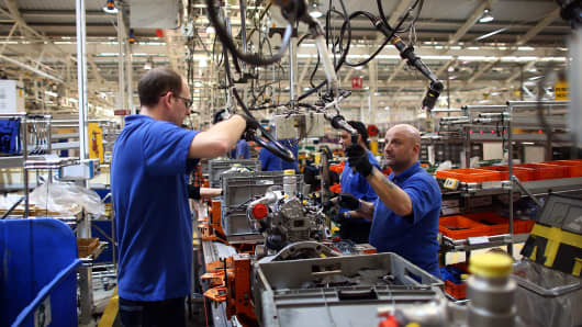 An employee works on an engine production line.