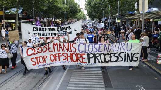 A group of people hold placards during a protest in Melbourne, Australia on January 22, 2015 to support the Manus Island asylum seekers and call for an end to offshore processing.