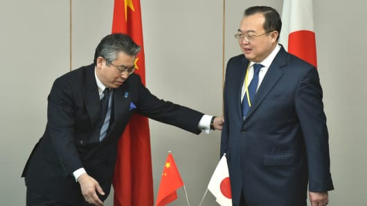 Japan's Foreign Deputy Minister Shinsuke Sugiyama (L) gestures as he welcomes China's Assistant Minister of Foreign Affairs Liu Jianchao (R) prior to the 13th round of Japan-China Security Dialogue at the Foreign Ministry in Tokyo on March 19, 2015.