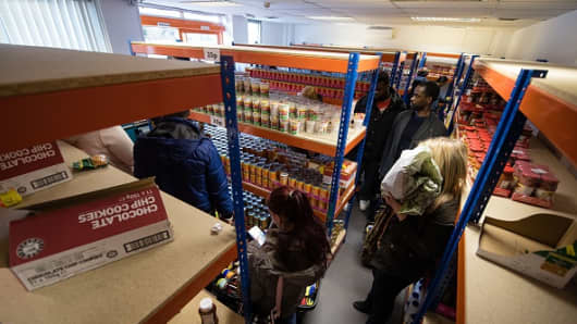 Shoppers queue to pay for their goods at the 'easyFoodstore' in north-west London on February 2, 2016.