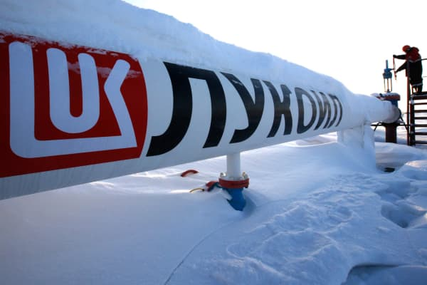 A worker checks the valve of an oil pipe at the Lukoil company owned Imilorskoye oil field outside the West Siberian city of Kogalym, Russia, January 25, 2016.