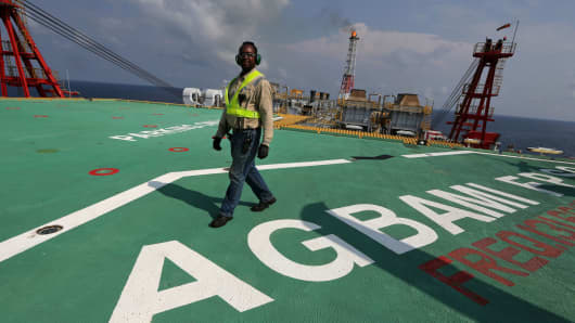 An employee walks across the helicopter landing deck aboard the Agbami storage and offloading vessel, operated by Chevron Corp., in the Agbami deepwater oilfield in the Niger Delta, Nigeria.