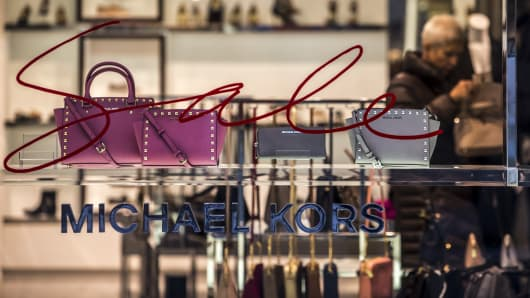 Leather handbags sit on display in the window of a Michael Kors Holdings Ltd. luxury store.