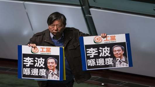 Lee Cheuk-yan, chairman of the Labour Party, holds signs protesting the disappearance of bookseller Lee Bo during the policy address of Hong Kong Chief Executive Leung Chun-ying in the chamber of the Legislative Council in Hong Kong, China, on Wednesday, Jan. 13, 2016.