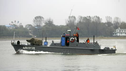 North Korean soldiers stand onboard a North Korean patrol boat along the Yalu River near the North Korean town of Sinuiju.