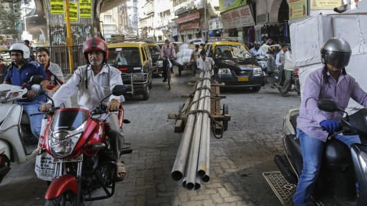 A porter transports metal pipes on a wooden handcart as people wait to cross a street in Mumbai, India, February 8, 2016. The Indian government on Monday forecast annual economic growth to accelerate to 7.6 percent in the fiscal year ending in March 2016 after Asia's third-largest economy grew 7.3 percent in the quarter to end-December.